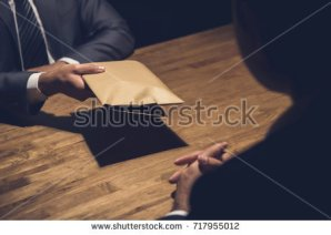 stock-photo-a-man-giving-bribe-money-in-a-brown-envelope-to-another-businessman-in-a-corruption-scam-717955012